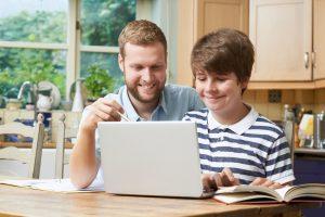 male-home-tutor-helping-teenage-boy-with-studies