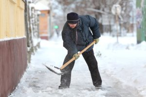 man shoveling snow on sidewalk